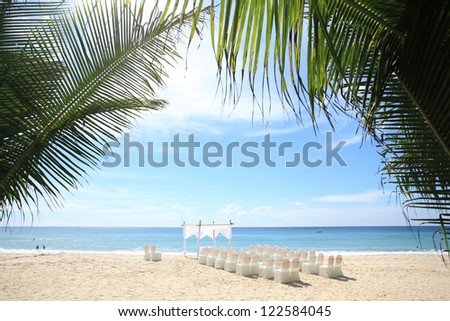 Wedding aisle with flowers decoration on the beach - stock photo