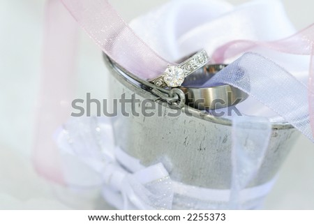 Wedding and engagement rings in a silver tin bucket.  Shallow D.O.F ? Rings in focus, foreground and background out of focus - stock photo