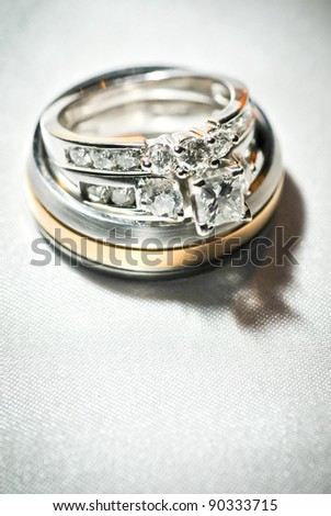 Wedding and Engagement rings on linen background, narrow focus macro shot. - stock photo
