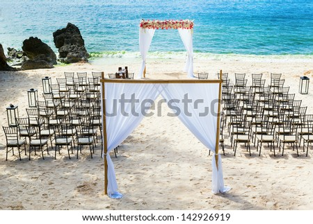Wedding arch and chairs on the beach - stock photo