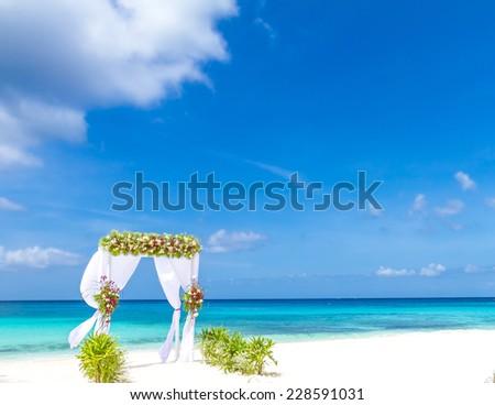 wedding arch and set up on beach, tropical outdoor wedding cabana on beach - stock photo