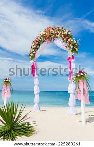 wedding arch, cabana, gazebo on tropical beach decorated with flowers, beach wedding decoration - stock photo