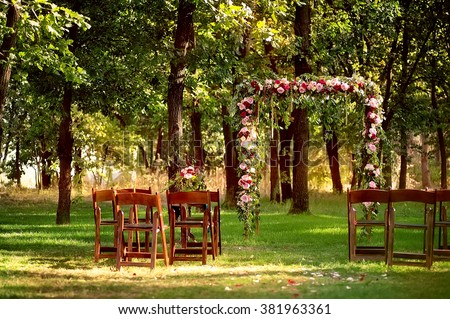 wedding arch decorated with flowers and wooden chairs in deep summer forest. picture with soft focus - stock photo