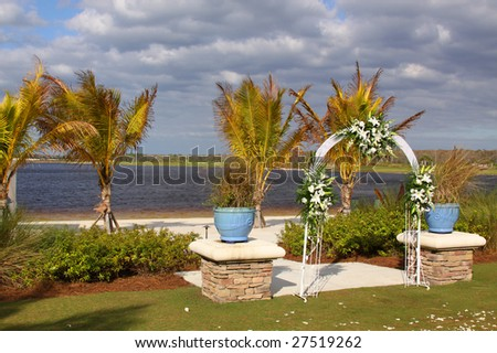 Wedding arch decorated with flowers in front of the palms and lake
