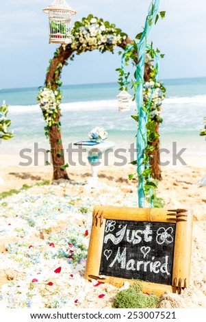 "wedding arch of flowers and ivy stands on the shore / beach. plate ""just married"" in the foreground - stock photo"