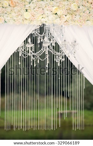 Wedding arch with chandelier and flowers - stock photo