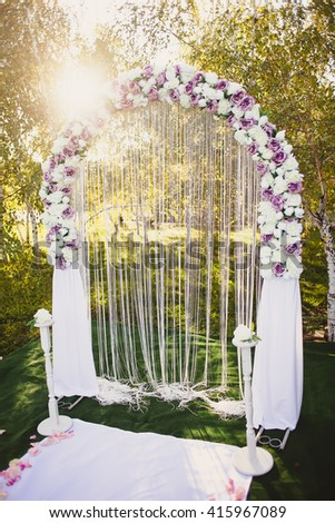 Wedding arch with purple flowers at sunset