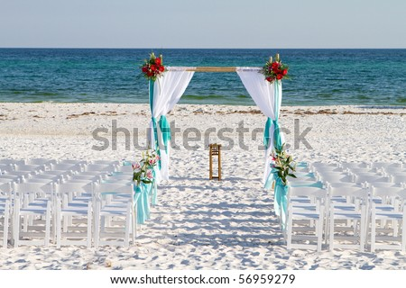 Wedding archway, chairs and flowers are arranged on the sand in preparation for a beach wedding ceremony. - stock photo