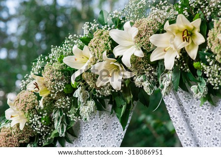 Wedding archway with flowers arranged in park  for a wedding ceremony. - stock photo