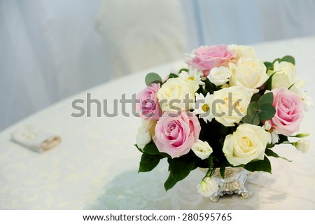 Wedding arrangement of a roses bouquet on a restaurant table
