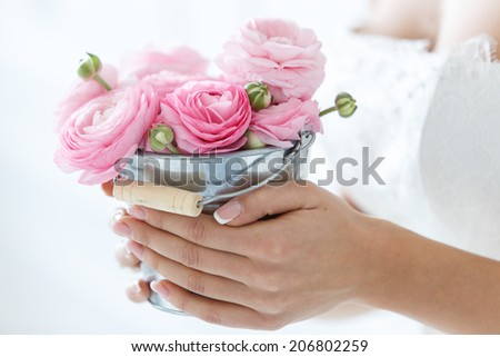 Wedding. Attractive bride holding pot with beautiful roses - stock photo