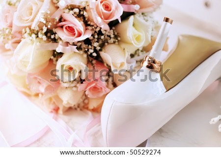 Wedding background from rings, bouquet and white shoes bridge - stock photo