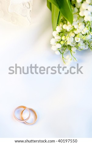 Wedding background with rings and lilies of the valley - stock photo
