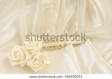 Wedding background with roses and a cage with birds on a fabric background. Romantic beige background for congratulations. - stock photo
