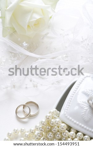 Wedding background with wedding bands, pearls and white rose.