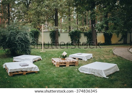 Wedding. Banquet. Decor. chill out area made of wooden storage pallets and soft pillows - stock photo
