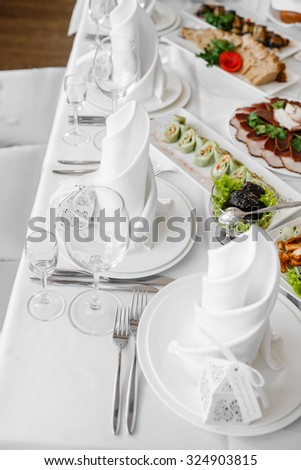 Wedding banquet  table with dishware and meal,  waiting for bride and groom.  - stock photo