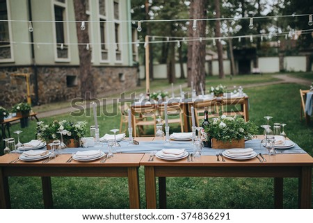 Wedding. Banquet. The chairs and table for guests, decorated with candles, served with cutlery and crockery and covered with a tablecloth. The table stands on a green lawn in the backyard banquet area - stock photo