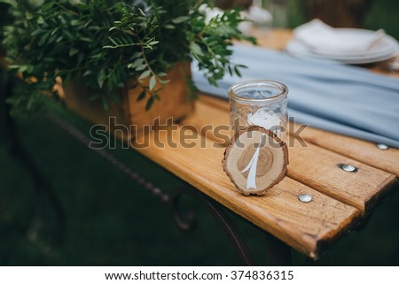 Wedding. Banquet. The plate with the table number of wood saw cut costs on a banquet table for guests, served cutlery and crockery and covered with a blue tablecloth. The table stands on the lawn - stock photo