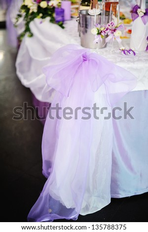 Wedding banquet. Violet bow on a decorated served table - stock photo