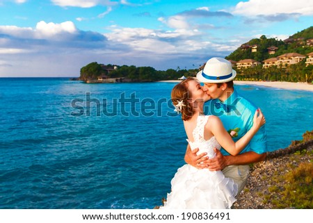 Wedding. Bbride and groom kissing on the tropical coast at sunset - stock photo