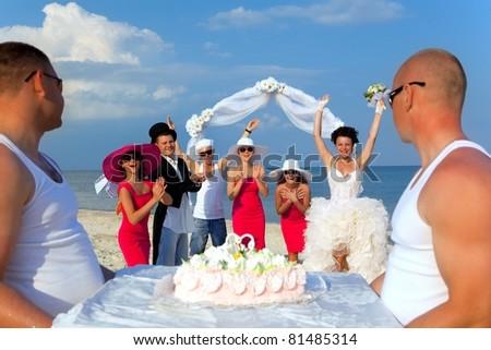 Wedding beach party. Presentation of wedding cake. - stock photo