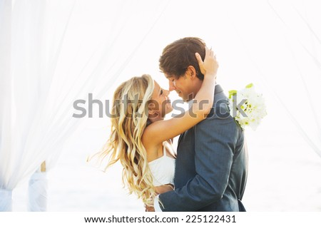 Wedding, Beautiful Romantic Bride and Groom Kissing and Embracing at Sunset - stock photo