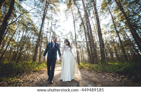 Wedding: beautiful young bride and groom standing in a park - stock photo