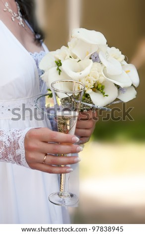 Wedding bouquet and glass with champagne in hands of the bride - stock photo