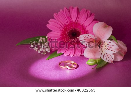 wedding bouquet and rings on magenta background - stock photo