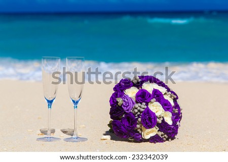 Wedding bouquet and two glasses of champagne on the sand. Blue sea in the background. - stock photo
