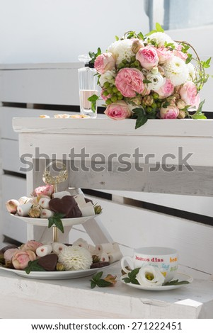Wedding bouquet, bottle of perfume, cup of tea and etagere with sweets - stock photo