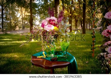 wedding bouquet, box with rings and wedding arch decorated with flowers  in deep summer forest. picture with soft focus - stock photo