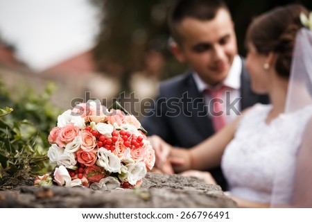 Wedding bouquet close up. Bride and groom in background. Shallow depth of field - stock photo