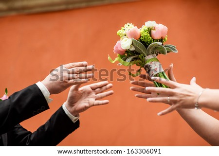 wedding bouquet flying to hands on red background - stock photo