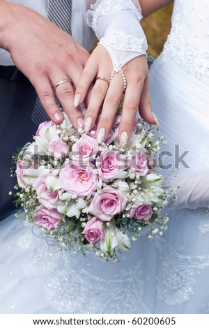 Wedding bouquet from tender roses, hands and rings - stock photo