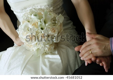 Wedding bouquet from white and pastel pink flowers, hands and ring - stock photo