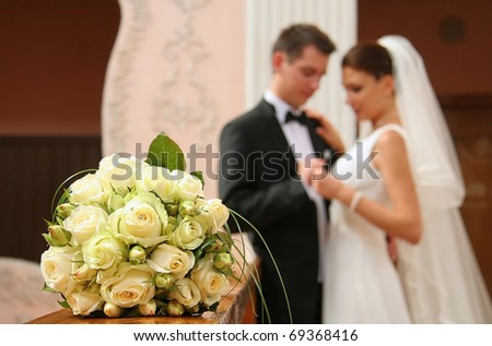 Wedding bouquet from white roses. Loving couple on a back background.