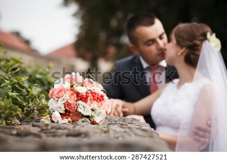 Wedding bouquet, groom and bride on background