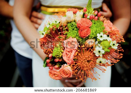 Wedding bouquet held by bride and groom. Shallow depth of field - stock photo