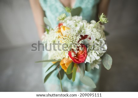 Wedding bouquet in a rustic style in the hands of the bride