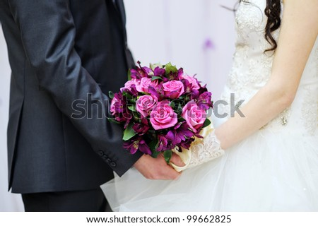 Wedding bouquet in hands of the bride and groom - stock photo