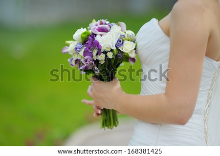 wedding bouquet in hands of the bride in profile purple flowers - stock photo