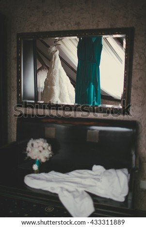 Wedding bouquet lies on a leather chair under the mirror in which reflects a wedding dress