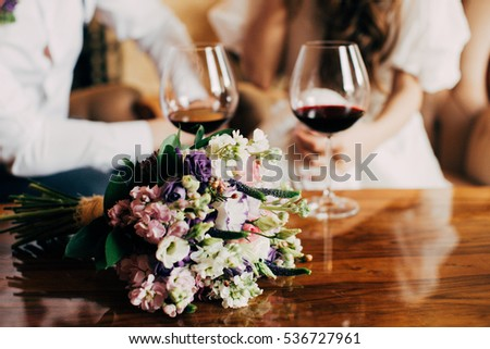 Wedding bouquet near to glass of red wine