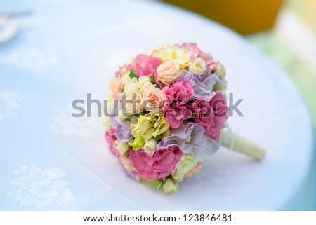 Wedding bouquet of bride - colorful flowers pink, white roses and yellow freesia lying on table at wedding on nature at summer day. Classic and elegant bridal decoration. close up of wedding bouquet - stock photo