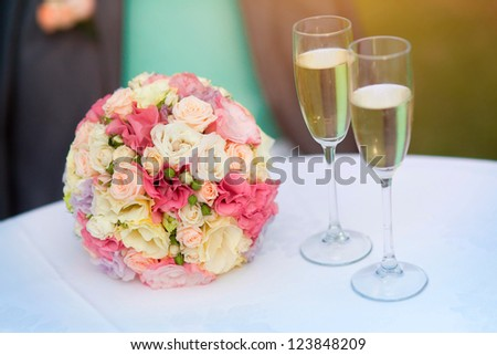 Wedding bouquet of bride near champagne glasses. colorful flowers pink, white roses,yellow freesia on table at wedding at summer day. Classic and elegant bridal decoration. close up of wedding bouquet