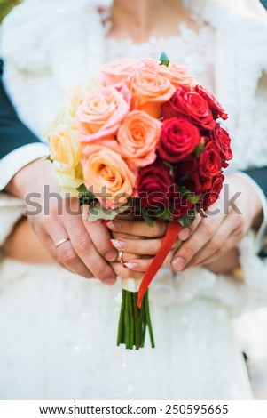 Wedding bouquet of flowers in hands of beautiful young bride and groom. focus on hands. Wedding decor. Wedding couple. - stock photo
