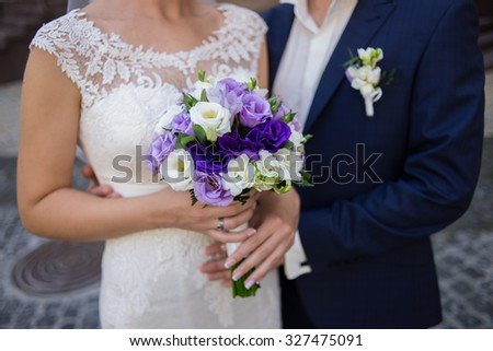 Wedding bouquet of flowers in the hands of the bride and groom - stock photo