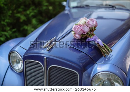 wedding bouquet of flowers lying on the trunk of a blue retro car - stock photo